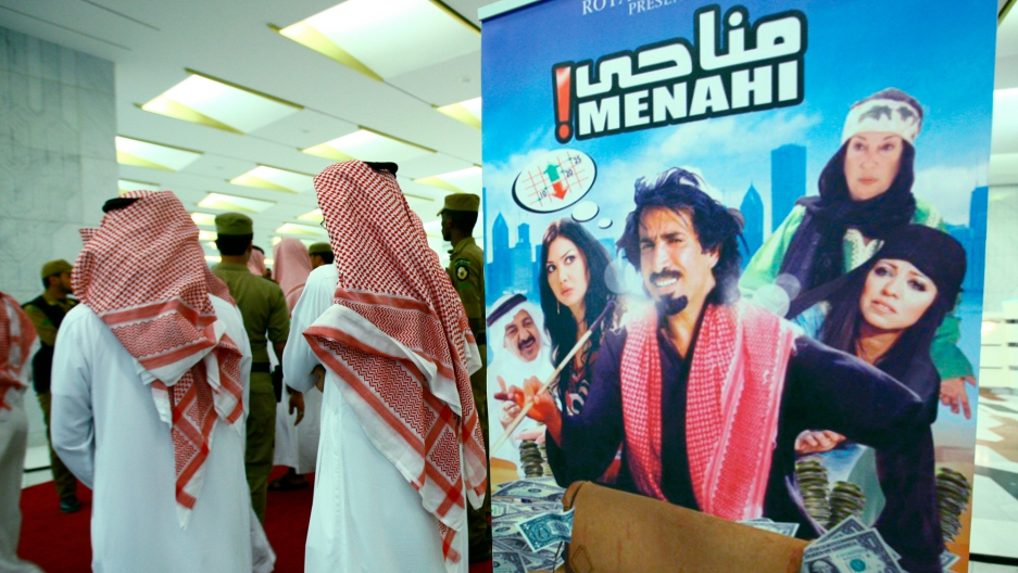 """Saudi religious men stand near a poster of the first Saudi film """"Menhai"""" at its opening at King Fahad Center in Riyadh June 6, 2009."""