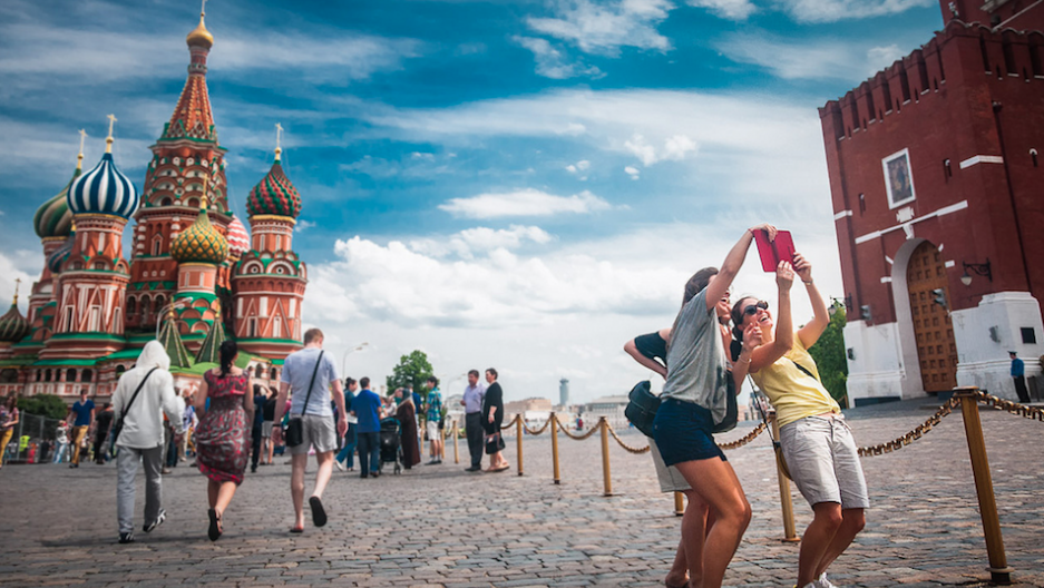 Tourists pose for a selfie outside of Saint Basil's Cathedral in Red Square.