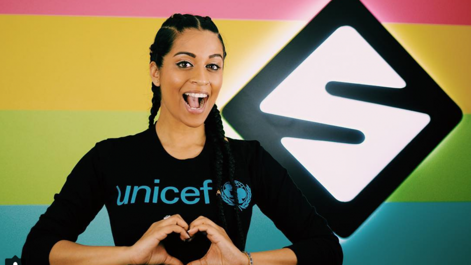 Lilly Singh poses with her hands in a heart symbol.