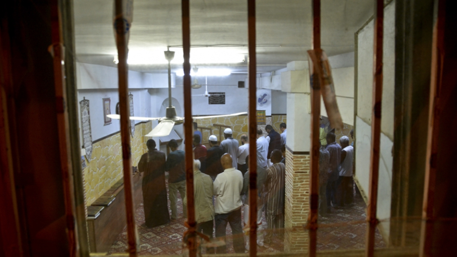 Muslim men gathered in a basement transformed into a a prayer room in the neighborhood of Agios Nikolaos, in Athens