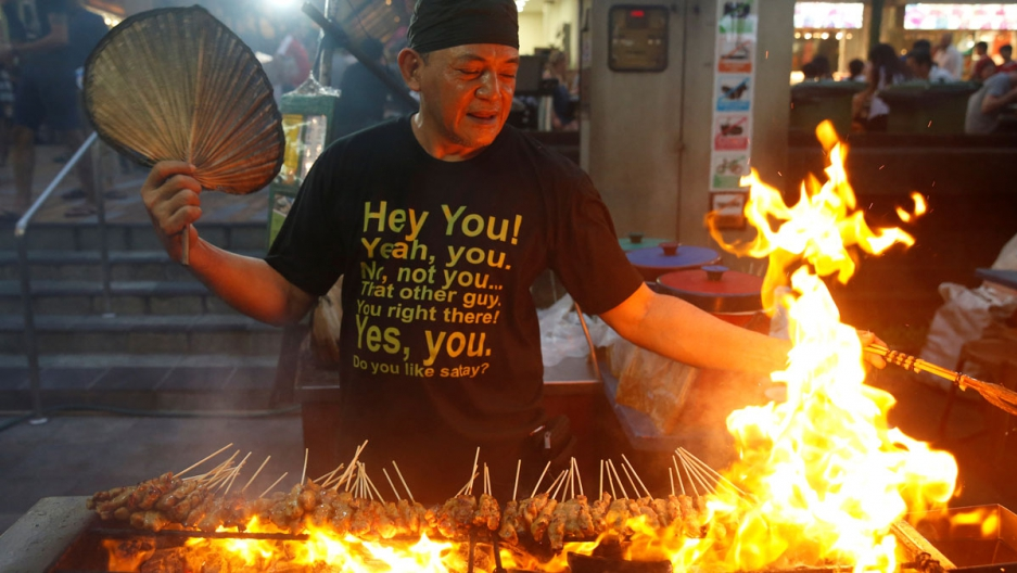 A stall helper mans a satay stand at Lau Pa Sat food center in Singapore.