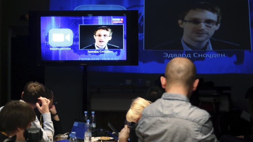 Journalists listen to a question posed by former US spy agency NSA contractor Edward Snowden, at a media center during Russian President Vladimir Putin's live broadcast nationwide phone-in.