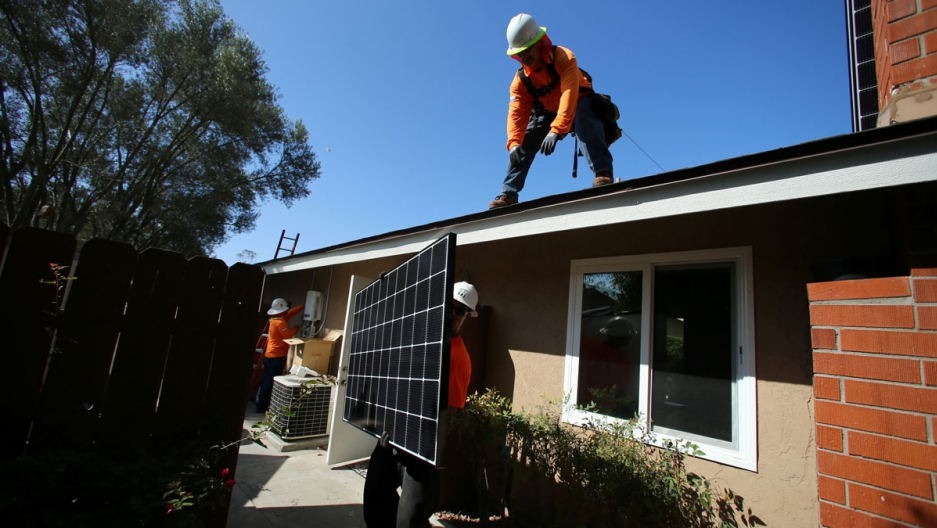 Tesla solar panels would replace the typical solar panel array, like this one being installed on home in Scripps Ranch, San Diego, California. Elon Musk wants to merge the two companies.