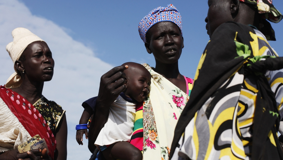 A woman carries a baby as she talks with other women at a food distribution in Minkaman, South Sudan.