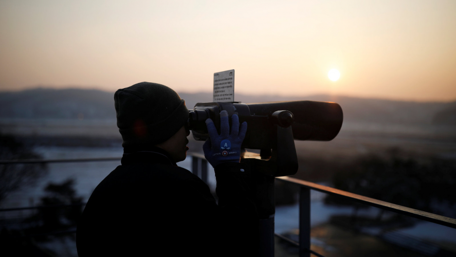 A man looks toward the north through a pair of binoculars near the demilitarized zone separating the two Koreas, in Paju, South Korea, Dec. 21, 2017.