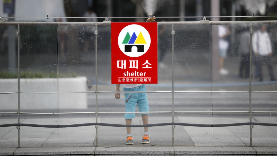 A boy plays behind a sign of shelter at an entrance of a subway station in Seoul, South Korea, August 11, 2017.