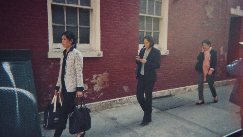 Three women walking on the sidewalk.
