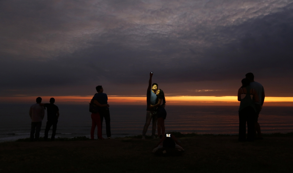 A couple takes a selfie as others observe the sunset at an oceanfront in the neighborhood of Miraflores in Lima.