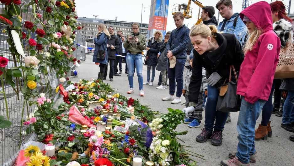 People gather at the crime scene near Ahlens department store in central Stockholm Saturday after a hijacked beer truck plowed into pedestrians.