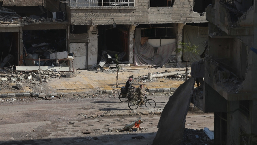 Men ride bicycles past damaged buildings along a street in the Duma neighborhood of Damascus, December 2013.