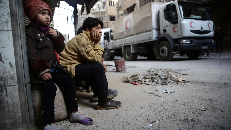 Children watch as an aid convoy of Syrian Arab Red Crescent drives through the besieged town of Douma, Eastern Ghouta, Damascus, Syria March 5, 2018.