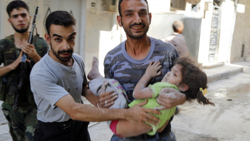 A man reacts as he carries a child who survived what activists said were barrel bombs dropped by forces of Syria's President Bashar Al-Assad in the Al-Fardous neighborhood of Aleppo, September 19, 2014.