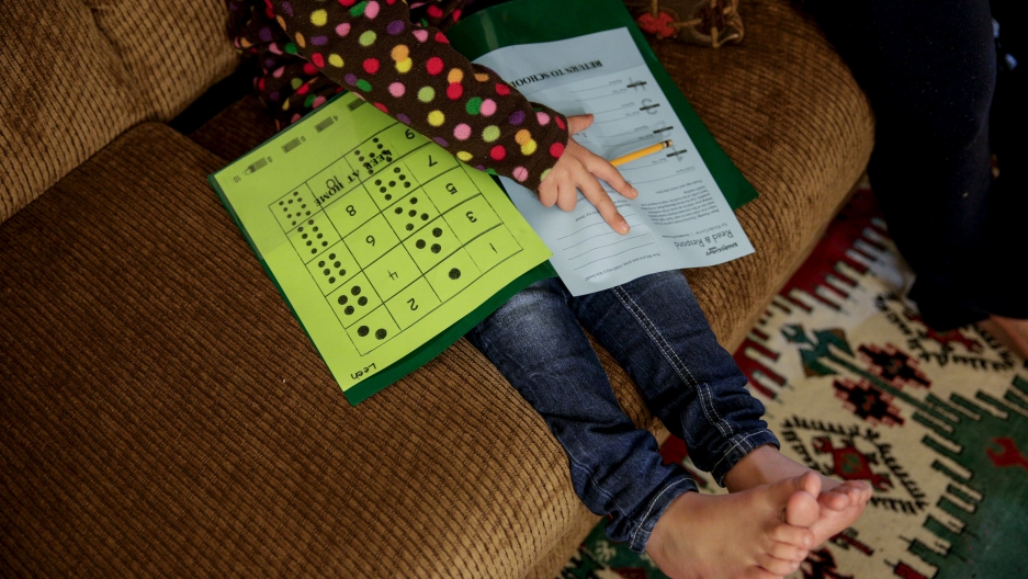 Five-year-old Syrian refugee Leen works on her homework at her new home in Sacramento, California.  Leen and her family fled violence in Syria three and a half years ago and arrived in Sacramento in September 2015 after living in Jordan. Her face is exclu