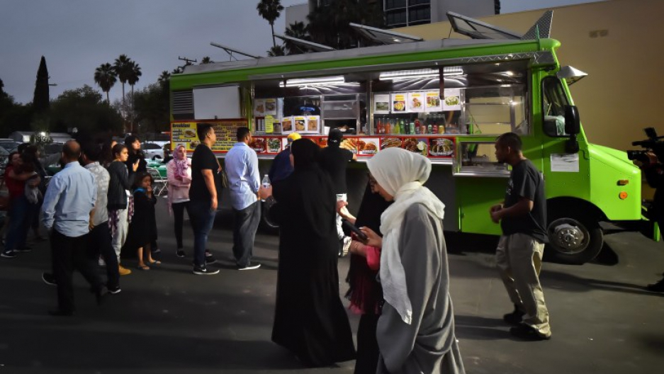 Members of the Islamic Center of Santa Ana lineup after sunset in front of a taco truck.