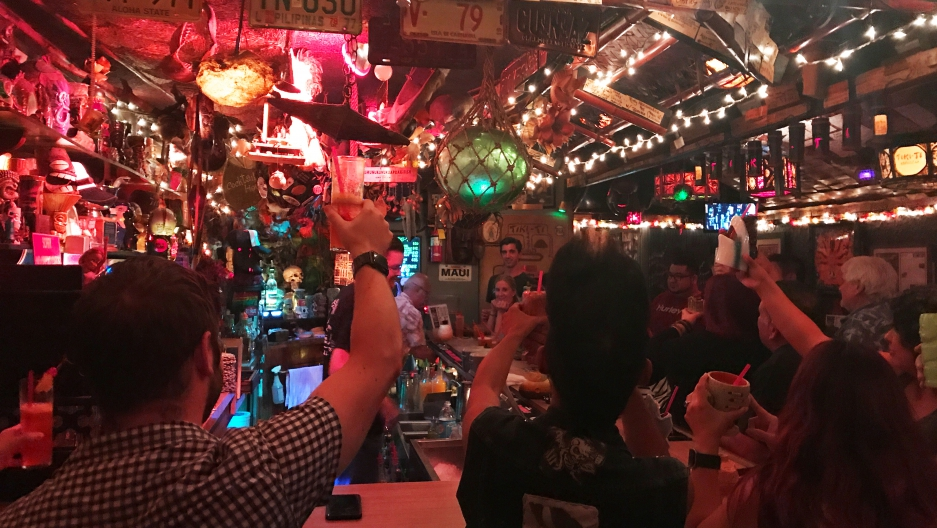Small and colorful bar with lights strung up, patrons raising their glass to the back wall