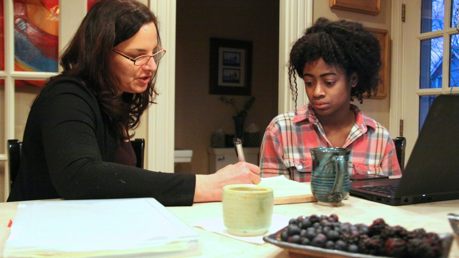 High school senior Mirabelle Espady and her mentor Marsha Kessler sit around the kitchen counter at Kessler's home, reviewing Mirabelle's college application.