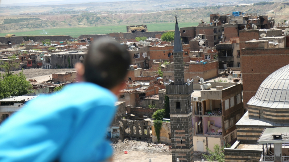 A boy looks at buildings which were damaged during clashes between Turkish security forces and Kurdish militants