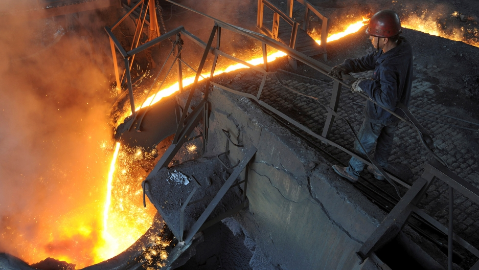 A worker monitors molten iron pouring into a furnace at steel manufacturing plant in Hefei, Anhui province, China.