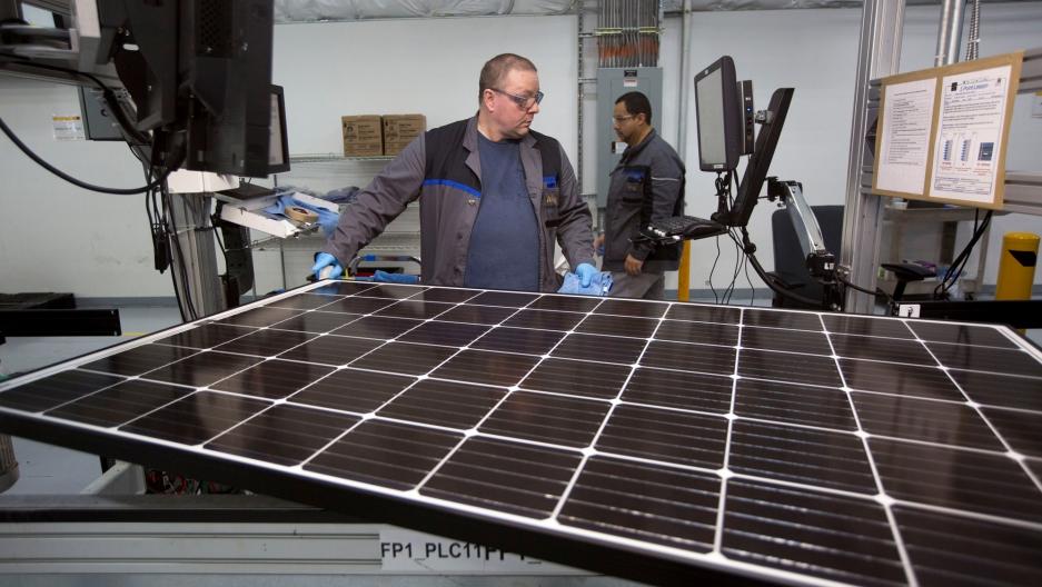 Production operator John White checks a panel at the SolarWorld solar panel factory in Hillsboro, Oregon.