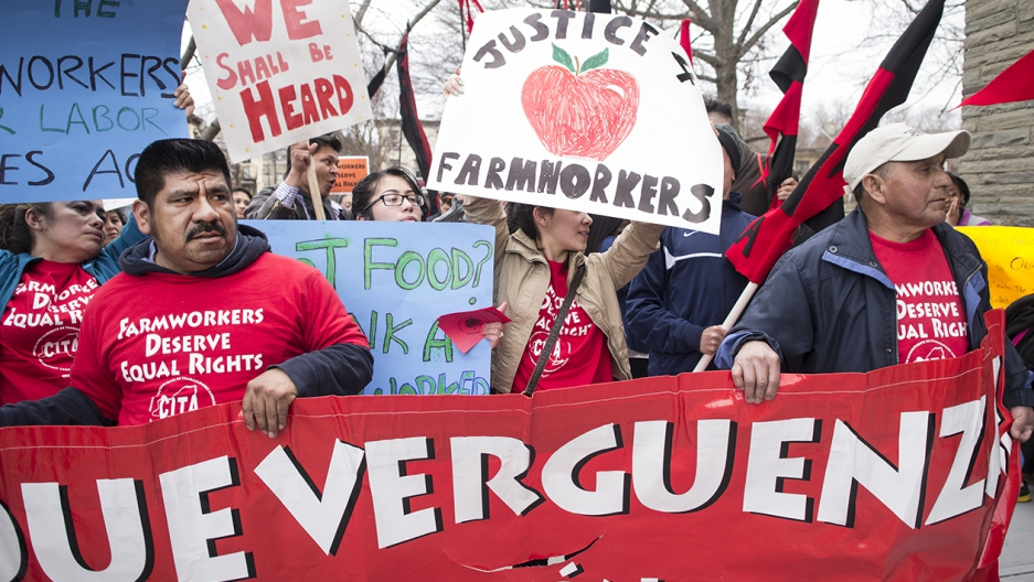 "Marchers hold up signs that say ""Justice for farmworkers"" and ""We shall be heard."""