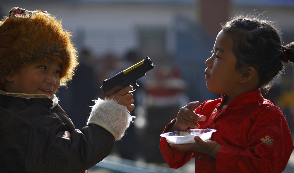 "A Tibetan boy points a toy gun towards a girl during the function organized to mark ""Losar"" or the Tibetan New Year at a Tibetan Refugee Camp in Lalitpur."