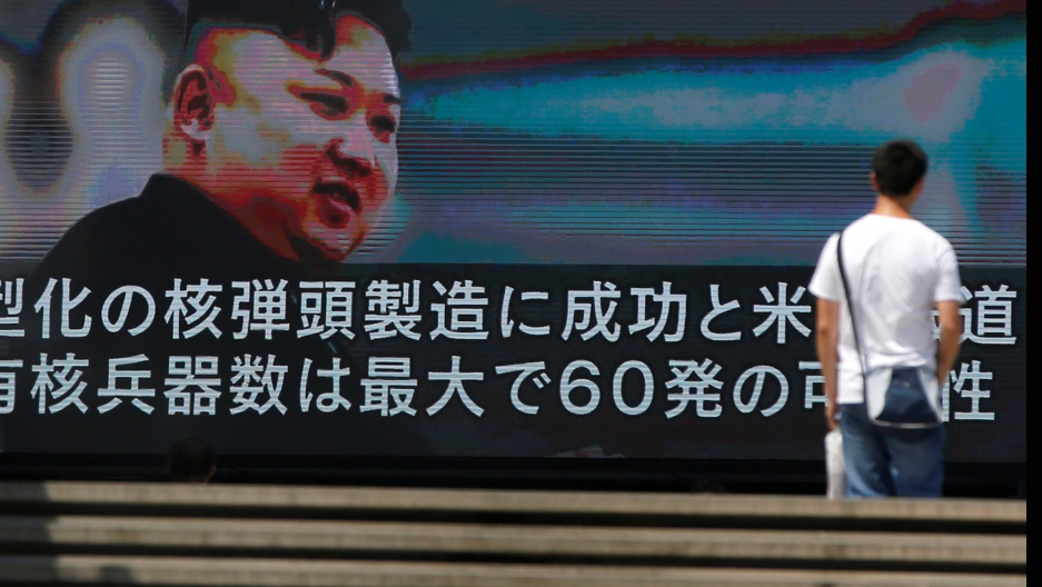 A passerby walks past a street monitor showing news of North Korea's fresh threat in Tokyo, Japan.