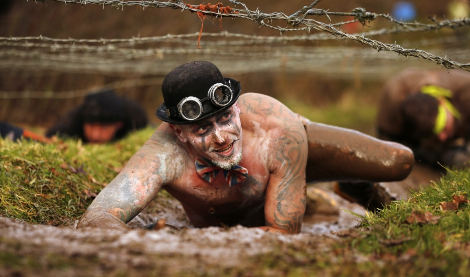 A competitor crawls beneath barbed wire during the Tough Guy event in Perton, central England February 1, 2015. The annual event to raise cash for charity challenges thousands of international competitors in a cross country run followed by an assault cour