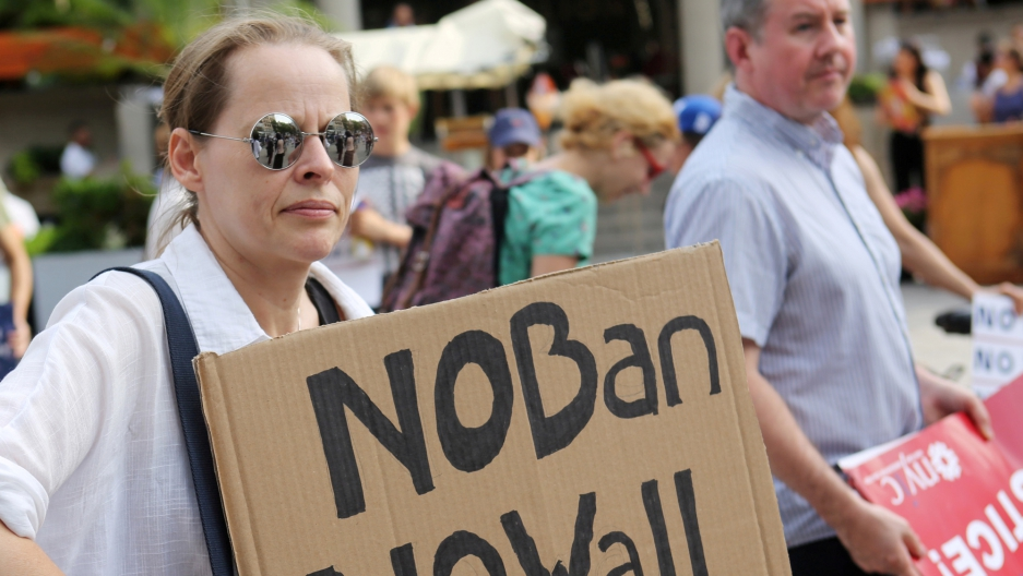 "A protester holds a sign reading ""No Ban, No Wall"" at a protest against President Donald Trump's travel ban."