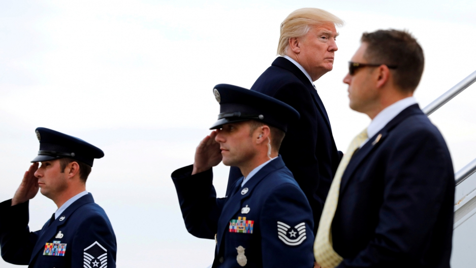President Donald Trump looks to his right while walking up the stairs to Air Force One with two Air Force officials soluting in the foreground.