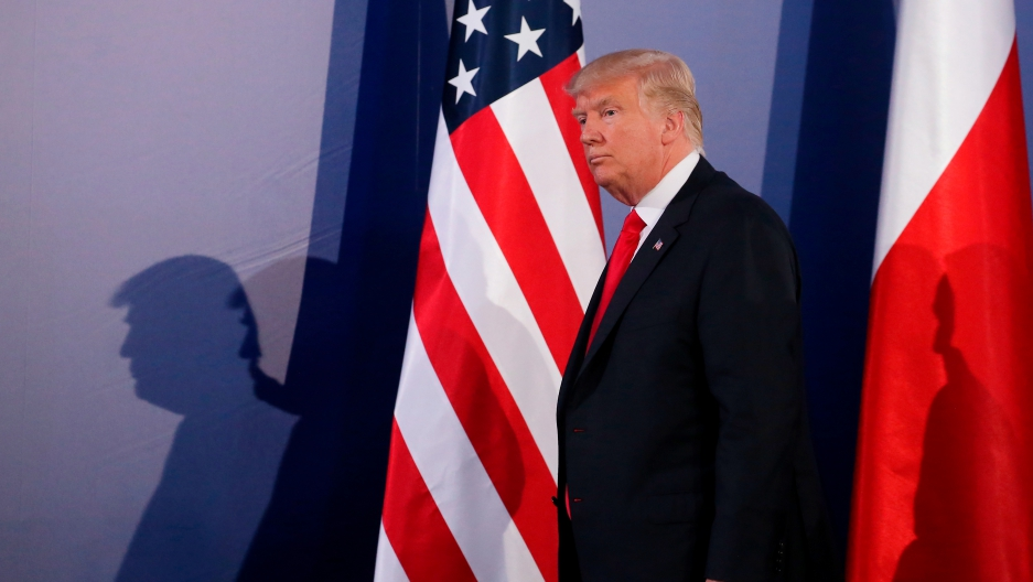 President Donald Trump walks past a US and Polish flag in Warsaw.