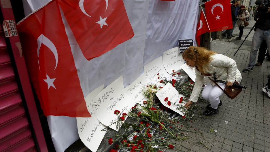 A woman places carnations at the scene of a suicide bombing at Istiklal Street, a major shopping and tourist district, in central Istanbul, Turkey.