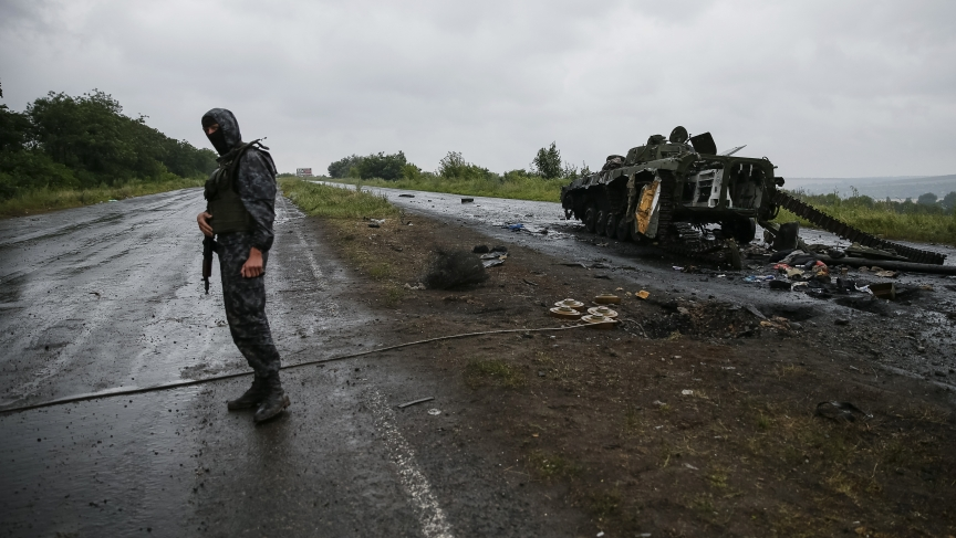 A Ukrainian soldier stands near a destroyed military vehicle of pro-Russian separatists just outside the eastern Ukrainian town of Slaviansk, July 7, 2014. REUTERS/Gleb Garanich