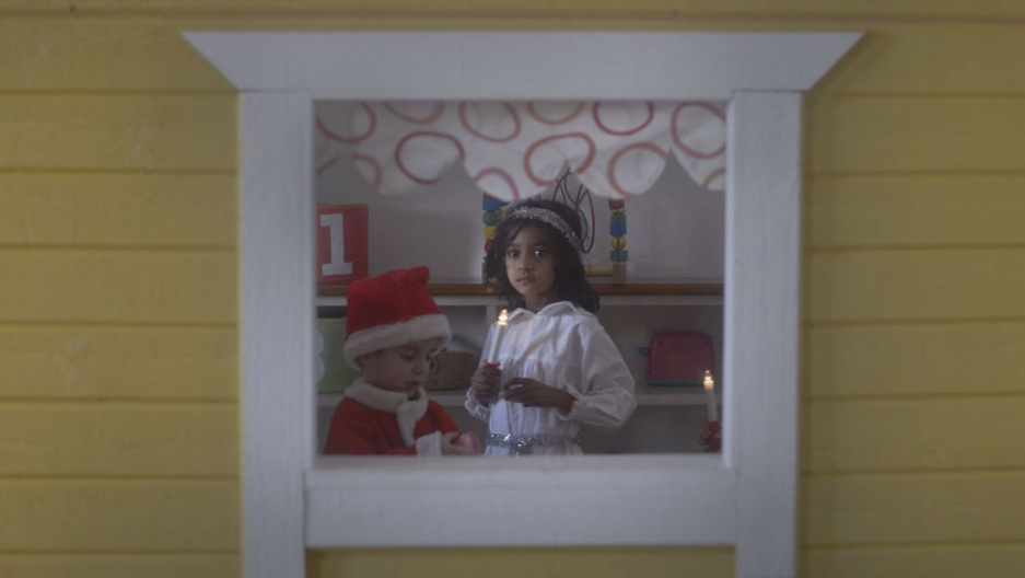 Aina from Sri Lanka looks through a window of a playhouse while she and her fellow preschoolers wait for the start of the Saint Lucia pageant.