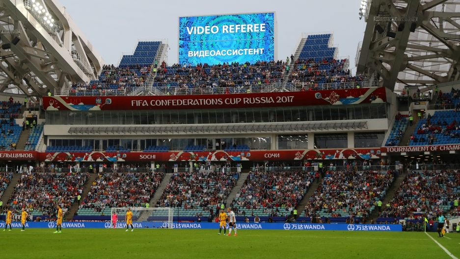 Players waiting for a decision after the referee asked for a video review of Australia's second goal against Germany during a Confederation Cup match in Sochi, Russia