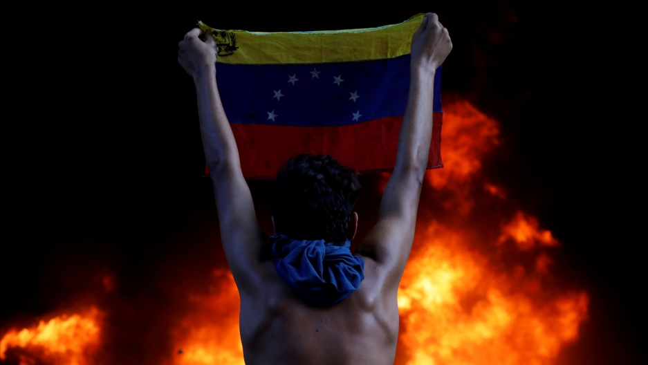 A protester holds a national flag while standing in front of a fire burning at the entrance of a building housing the magistracy of the Supreme Court of Justice, during a rally against Venezuela's President Nicolas Maduro, in Caracas, Venezuela, June 12,