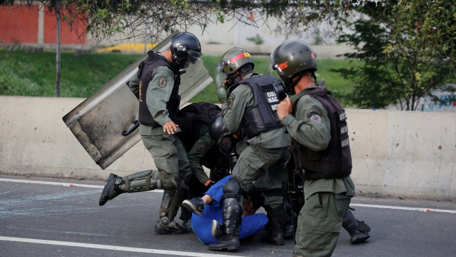 An opposition supporter is detained by riot police during a rally against President Nicolas Maduro in Caracas, Venezuela.