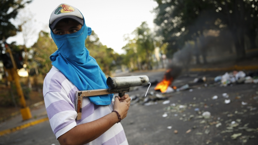 A demonstrator stands guard with a rudimentary mortar in front of a burning barricade during protests against Nicolás Maduro's government in San Cristóbal, Venezuela.