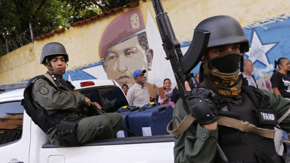 One soldier sits in a truck and another stands with riffle in hand in front of a mural of the late Venezuelan President Hugo Chavez.