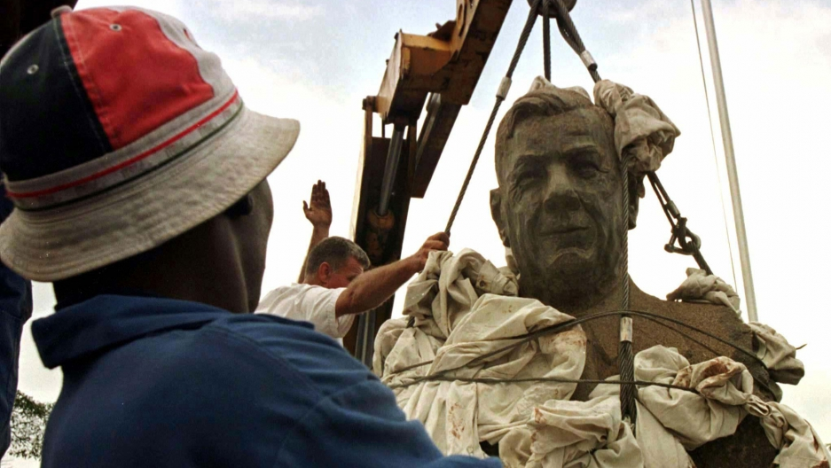 A man watches the bust of South Africa's Apartheid Architect, Hendrik Verwoerd, being removed from the entrance of Pretoria's main hospital named after him.