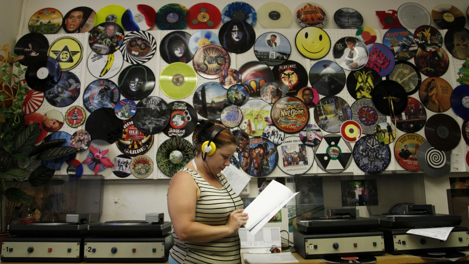 Employee Petra Kottova checks the sound quality of a pressed vinyl record at the GZ Media factory in Lodenice August 1, 2013