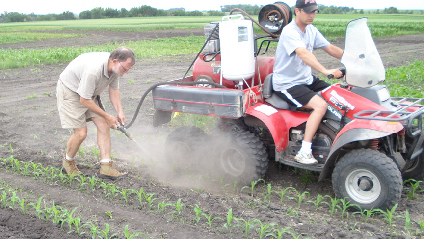 Jim Eklund and Frank Forcella conduct an early test of the concept with a single-nozzle blaster. Jim is driving the ATV and Frank is applying the grit.