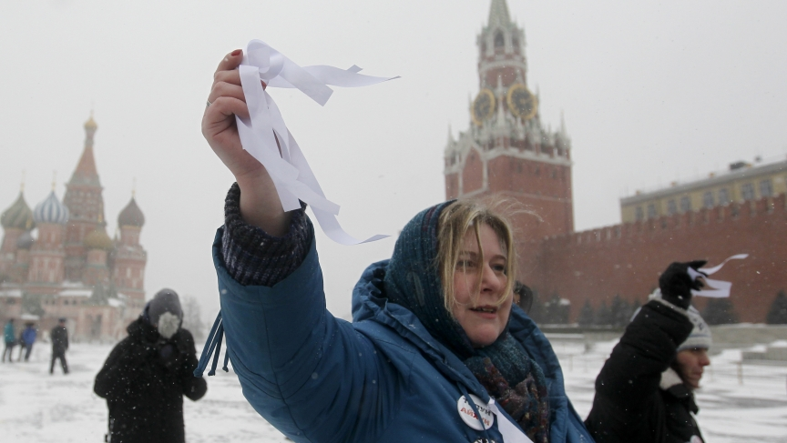 An activist holds white ribbons, the symbol of the opposition movement, during a protest  on Moscow's Red Square March 24, 2013. The action was organised to show solidarity for these arrested at opposition rallies in May 2012.