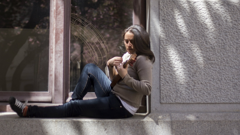 A woman sits on a window sill playing the jarana
