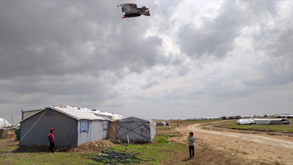 Children play with a kite at a shelter for displaced Yazidis on Mount Sinjar, northern Iraq.