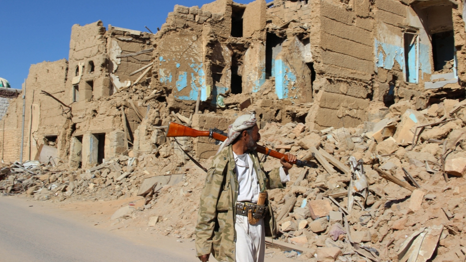 A Houthi armed man walks past destroyed houses in the old quarter of the northwestern city of Saada, Yemen, on Jan. 11.