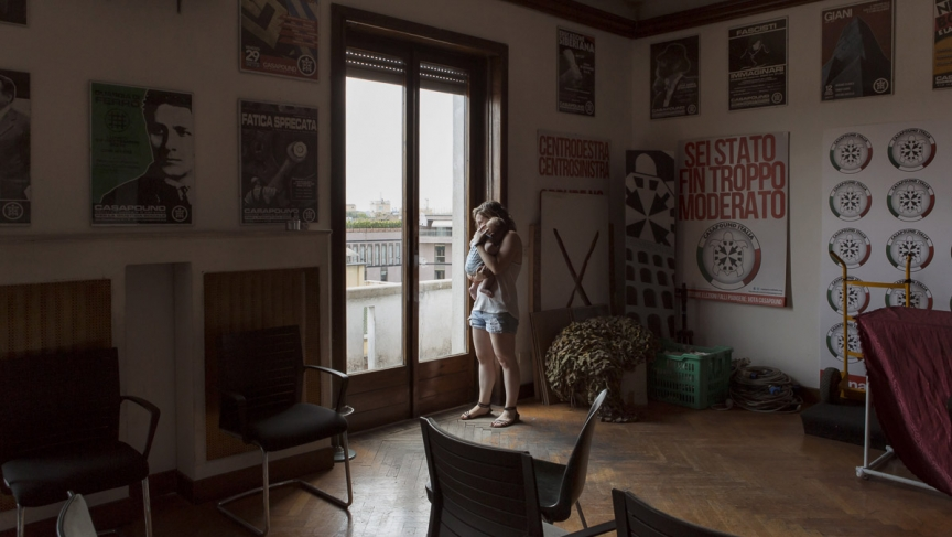 Estella and her four-month-old inside their squat house, which is also the headquarters of CasaPound, Italy's largest neo-Fascist movement. The walls are covered in ultra-nationalist posters.