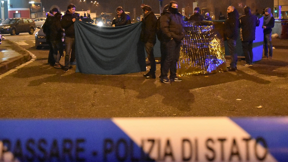 Italian police officers work next to the body of Anis Amri