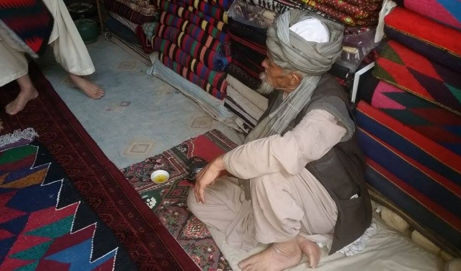 "A man selling handwoven rugs in the city of Quetta, in western Pakistan. While the ""war rugs"" are in demand in Western countries, their value in the local Pakistani market is very low."