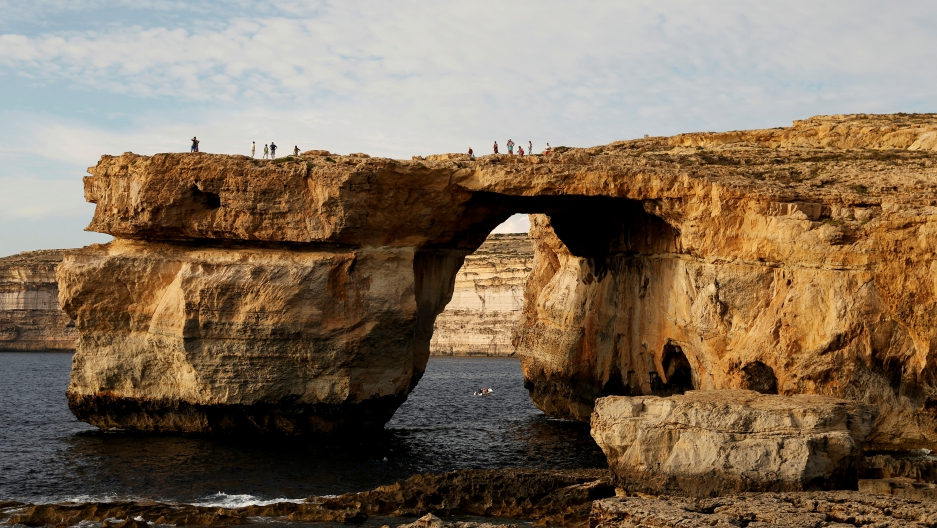 Tourists walk on the Azure Window, a 50 metre high rock arch, at Dwejra Point cliffs on the west coast of the Maltese island of Gozo September 23, 2016.