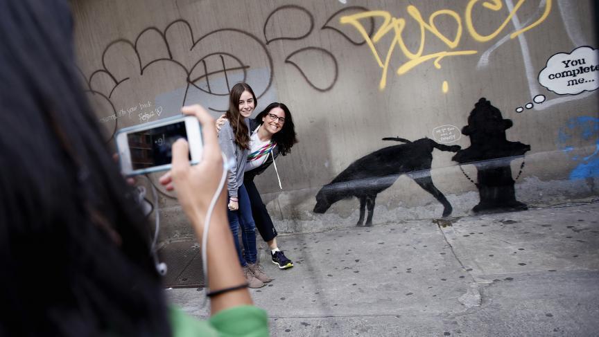 Two women have their picture taken next to new artwork by British graffiti artist Banksy on West 24th street in New York City, October 3, 2013. The anonymous artist recently announced a month-long residency in New York.